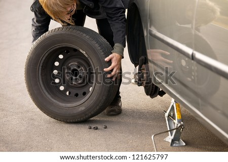 Changing wheel on a car on the roadside - stock photo