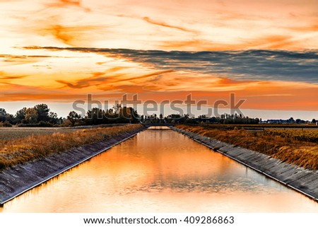 Channel to divert river water for irrigation of cultivated fields - stock photo