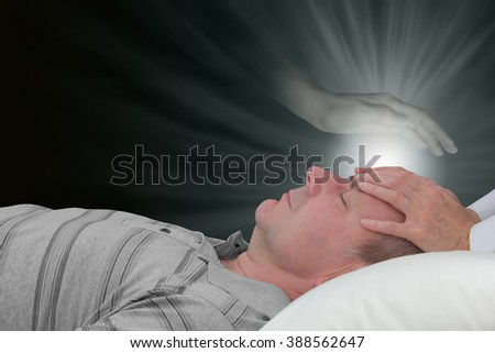 Channeling healing with a spirit guide - female hands laid on a male patient's forehead with an ethereal ghostly spirit hand hovering above and a glow of healing light  energy on a dark background - stock photo