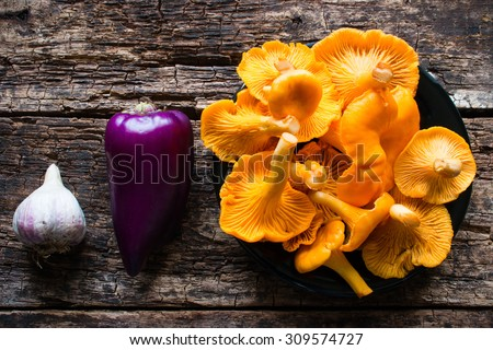 chanterelle mushrooms, garlic and pepper on a wooden background - stock photo