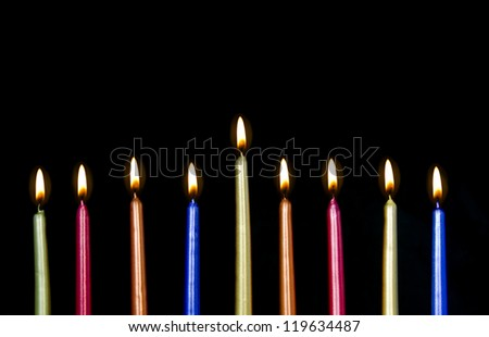 Chanukah candles all in a row. Bright, shiny multicolor candles for the Jewish holiday of Chanukah. All lit, isolated on a black background, horizontal view. - stock photo