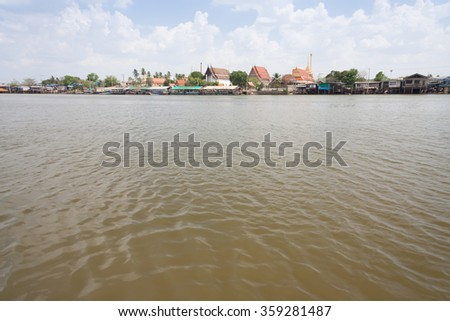 Chao Phraya river in Bangkok, Thailand,with temple and thai houses in the background. - stock photo