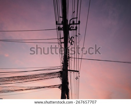 Chaotic electric wire with nest on pole and orange sky background - stock photo