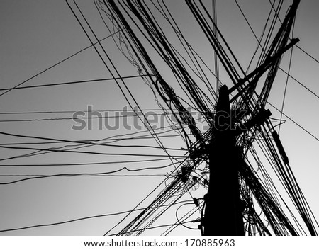 chaotic wire on pole with sky background in black and white - stock photo