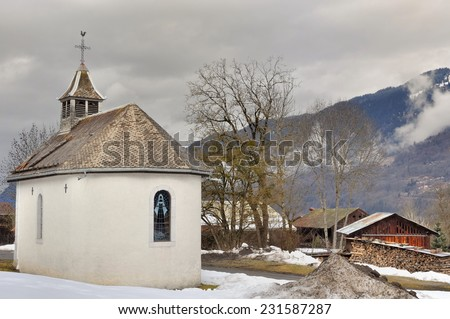chapel in a mountain village in winter - stock photo