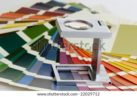 Characteristic image for the pre-press and printing industry. Linen tester withand colour sample. - stock photo
