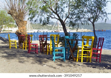 Characteristic restaurant with table and colorful chairs on the beach - stock photo