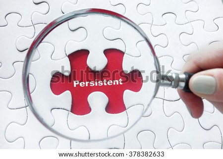 Characteristic word Persistent with hand holding magnifying glass over jigsaw puzzle - stock photo