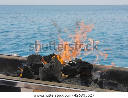 Charcoal BBQ barbecue coals burning on fire with tropical ocean background - stock photo