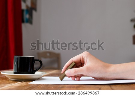 charcoal drawing. Hand holding charcoal crayon at paper at wooden table with coffee - stock photo