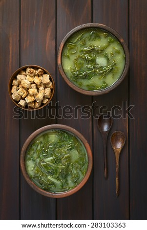 Chard soup in rustic bowls and a small bowl of croutons with two wooden spoons, photographed overhead on dark wood with natural light - stock photo