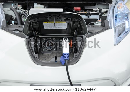charge point on electric car with charger - stock photo