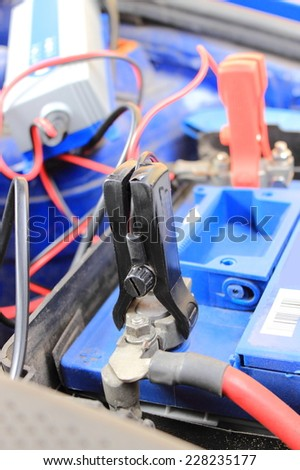 Charger with cables uses to charge dead car battery - stock photo