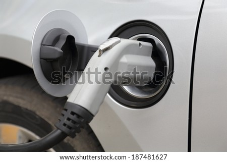 Charging an Electric Car. Close up of the power supply plugged into an electric car being charged.  - stock photo