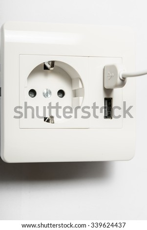 Charging. Somthing charged from the socket, with two usb-charger ports. - stock photo