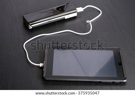 Charging tablet in front of portable rechargeable battery on black desk - stock photo
