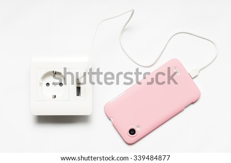 Charging. The smartphone charging from the socket, with two usb-charger ports. - stock photo