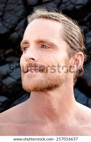 Charismatic attractive shirtless blond man with a beard and moustache staring thoughtfully to the side with a quiet smile and faraway dreamy expression - stock photo