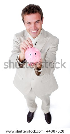 Charismatic businessman saving money in a piggybank against a white background - stock photo