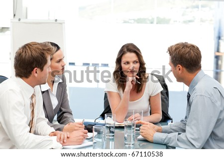 Charismatic businesswoman at a table with her team during a meeting - stock photo