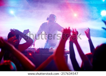 Charismatic disc jockey at the turntable - stock photo
