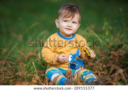 charismatic little baby sitting on the grass in the park outdoors  - stock photo