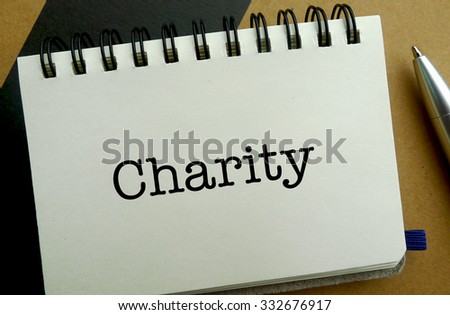 Charity memo written on a notebook with pen - stock photo