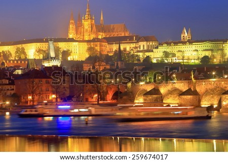 Charles bridge and distant Prague Castle reflected by the Vltava river by night, Prague, Czech Republic - stock photo