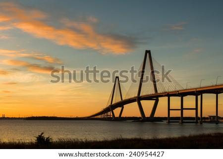 CHARLESTON, SOUTH CAROLINA - DECEMBER 7: Sunset at the Arthur Ravenel Jr. Bridge across the Cooper River on December 7, 2014 in Charleston, South Carolina - stock photo