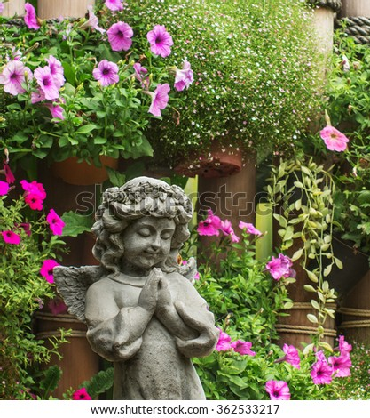 charm angel sculpture with flower in the garden - stock photo
