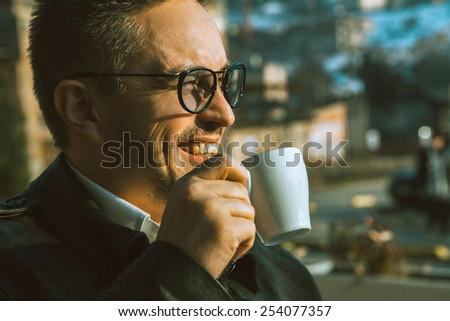 Charming adult man smiling and drinking coffee outdoors - stock photo