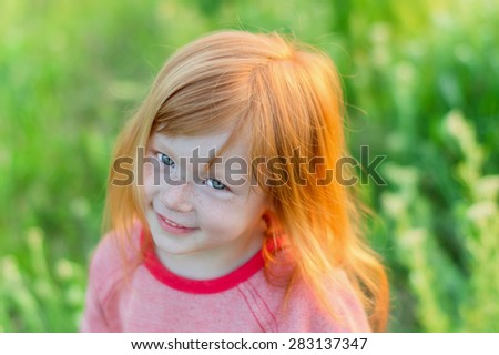 charming and beautiful little girl with blue eyes and red hair smiling on a background of green grass - stock photo