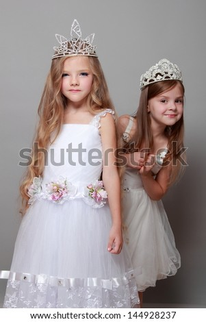Charming and elegant little girls dressed in white and wearing a crown on Beauty and Fashion - stock photo