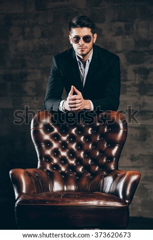 Charming and elegant. Young handsome man in suit and sunglasses leaning on leather chair and looking at camera while standing against dark grey background - stock photo