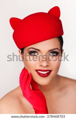 Charming and flirting girl in a funny red hat, the image of a playful cat - stock photo