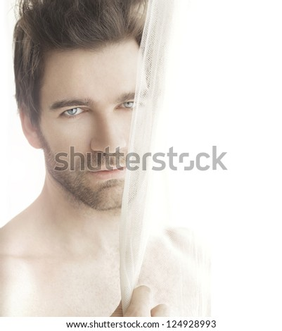 Charming and handsome man next to bright window - stock photo