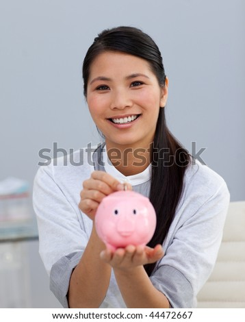 Charming asian businesswoman saving money in a piggybank in the office - stock photo