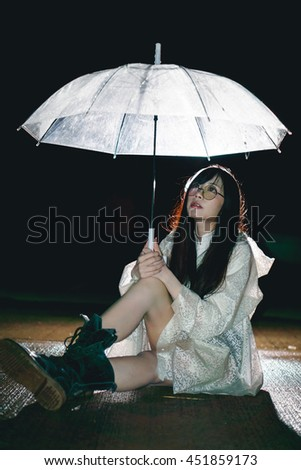 Charming Asian girl  with umbrella and raincoat at night - stock photo