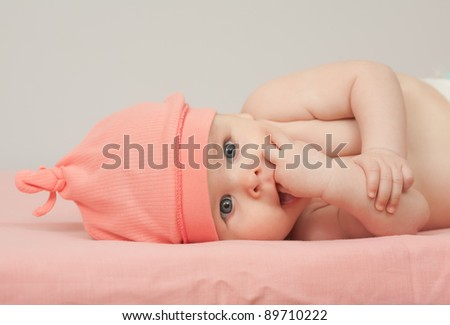 Charming baby. Baby girl in pink hat lies on back and sucks her fingers - stock photo