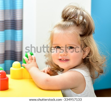 Charming baby girl playing with toys. Indoors. Room  interior. - stock photo