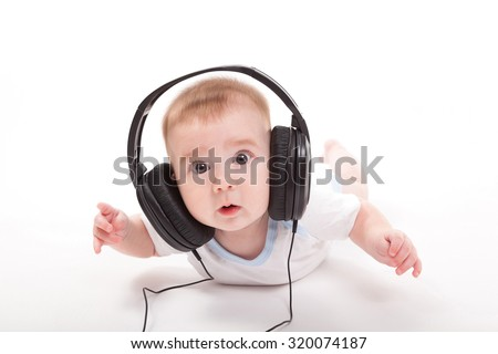charming baby on a white background with headphones listening to music. Photo from the depth of focus and artistic blur - stock photo