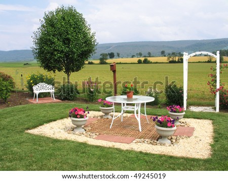 Charming backyard patio in rural setting of fields backed by mountains - stock photo
