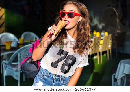 Charming beauty.Beautiful young woman eating a big sweet ice cream in red sunglasses, shorts, sports bag on his shoulder, standing   outside in summer. - stock photo