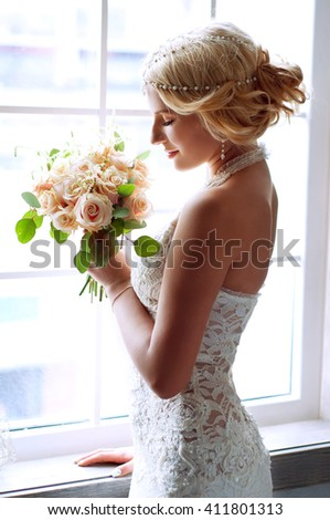 Charming blond bride waiting near the window for her groom wearing white lace dress and pearl headpiece  - stock photo