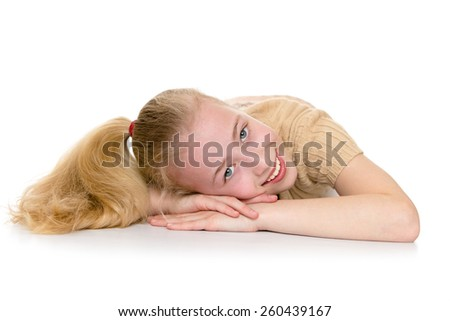 Charming blond girl with a long tail on the head, cute smiling at the camera while lying on the floor - isolated on white. - stock photo