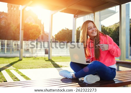 Charming blonde female student pointing to open laptop while looking for someone at campus, happy female teenager having fun while sitting on the bench with open computer outdoors, flare bright sun - stock photo