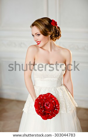 Charming blonde girl with beautiful smile in a white lace dress and a bouquet of red roses stands on a light background in the Studio and smiling - stock photo