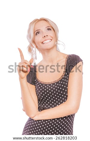 Charming blonde in dark dress shows fingers upwards and smiles, isolated on white background. - stock photo