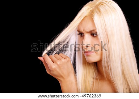 Charming blonde is not happy with fragile hair, it is isolated on black background. - stock photo