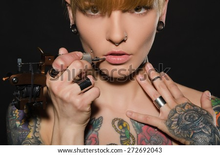 charming blonde with tattoo machine and for them, dark background - stock photo